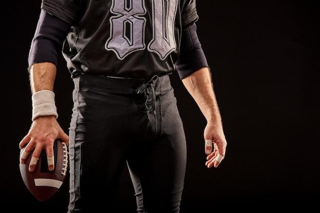 Средняя часть игрока в американский футбол в черной форме с мячом на черной поверхности, копирование пространства, передний план