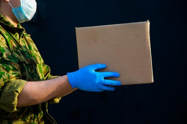 軍はあなたの家に食べ物を届けます。年金受給者、貧困層、人口への支援。ゴム手袋の宅配便が黒い背景にボックスを保持しています。