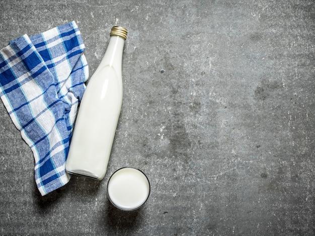 병과 유리 잔에있는 우유. 돌 테이블에.