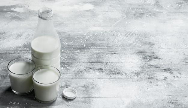 Молоко в бутылке. на деревенской поверхности.