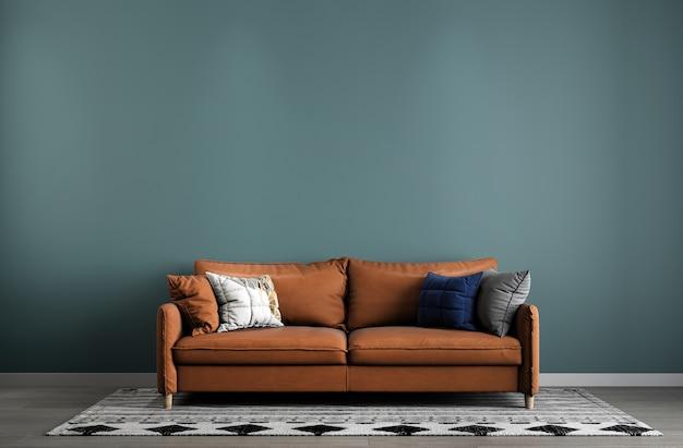 最小限のリビングルームと革張りのソファと緑の壁