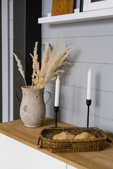 Минималистичный дизайн интерьера кухни оформлен засушенными цветами в вазе свечей.