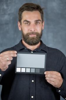 모델은 손에 카드를 들고 중성 회색 음영으로 색상을 확인합니다.