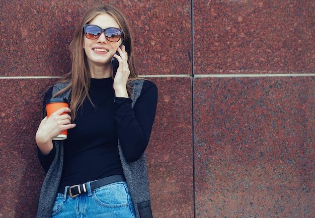 Модель стоит у стены и разговаривает по телефону