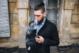 The model vaper vaping a vaporizer outdoors. Safe smoking. Young vaper.