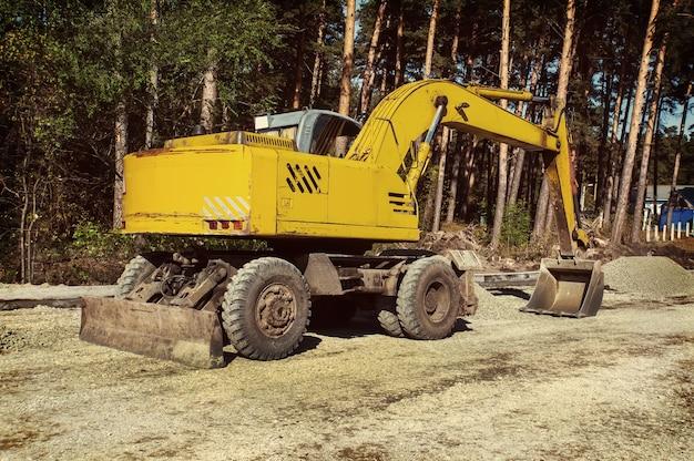 현대 굴착기는 건설 현장에서 굴착 작업을 수행합니다. 바퀴에 노란색 굴 삭 기입니다. 프리미엄 사진