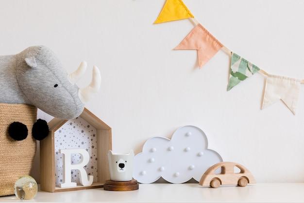 コピースペース、木製の車、ぬいぐるみ、雲のあるモダンなスカンジナビアの新生児用ルーム。ぶら下がっている綿の旗と白い星。白い壁のミニマルで居心地の良いインテリア。