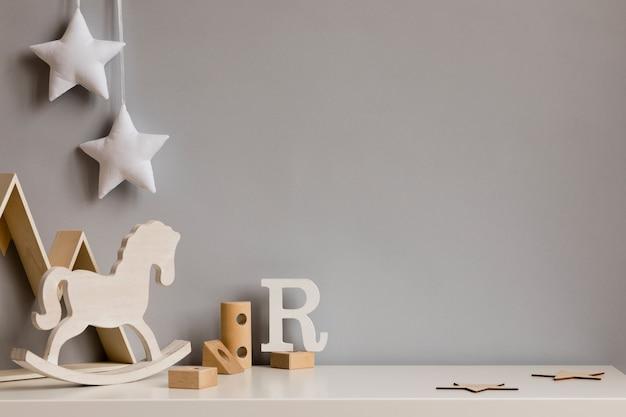 Современная скандинавская комната для новорожденных с копией пространства, деревянными игрушками, плюшевыми животными, детскими аксессуарами, облаками и подвесной гирляндой.