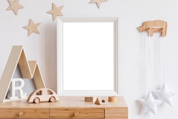 프레임, 나무 자동차, 봉제 장난감, 어린이 액세서리, 구름 및 교수형 화환이있는 현대적인 스칸디나비아 신생아 방. 흰색 벽이있는 미니멀하고 아늑한 인테리어.