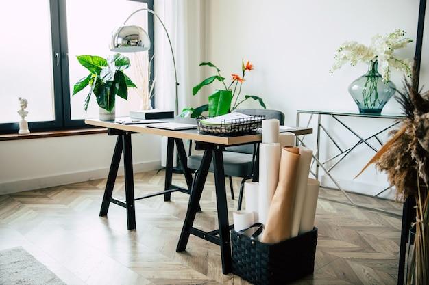 Современный стильный стол в интерьере рабочего места с множеством бумаг, документов и предметов интерьера.