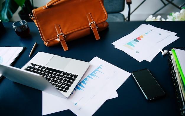 多くの書類、書類、ラップトップ、スマートフォン、カップ、ビジネスバッグを備えた職場のインテリアにあるモダンでスタイリッシュなテーブル
