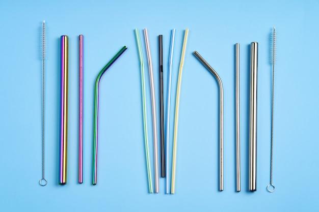 Современная тенденция к заботе об окружающей среде. набор многоразовых металлических соломинок для напитков различной формы и диаметра с чистящим инструментом по сравнению с обычными пластиковыми соломинками.