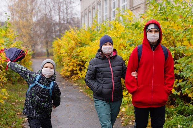 길거리에서 보호 마스크를 쓰고 걷는 두 아들과 엄마
