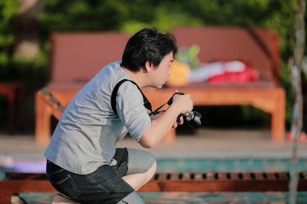 アジアのタイのプロの写真家の瞬間はひざまずいて、素晴らしい写真を撮るために待っています。