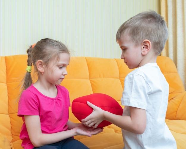 Момент вручения подарка. мальчик дает красную подушку в форме сердца девушке, сидящей на диване. с днем рождения, с днем сестры, с днем девочек