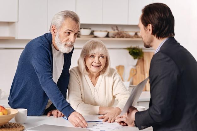 결정을 내리는 순간. 노령 고객과 대화하고 집을 팔면서 중요한 서류를 사용하는 숙련 된 숙련 된 부동산 중개인
