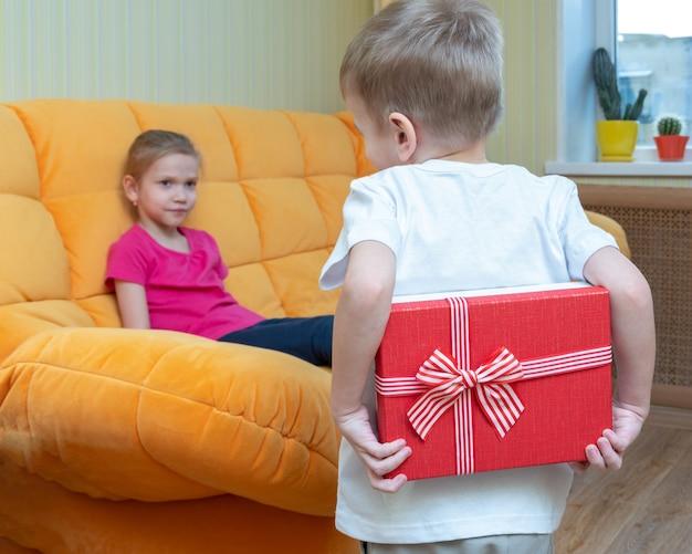 선물을 기다리는 순간. 소년은 소파에 앉아 있는 소녀에게 주기 위해 등 뒤에 빨간 선물 상자를 들고 있습니다. 생일 축하해, 행복한 자매의 날, 행복한 소녀의 날