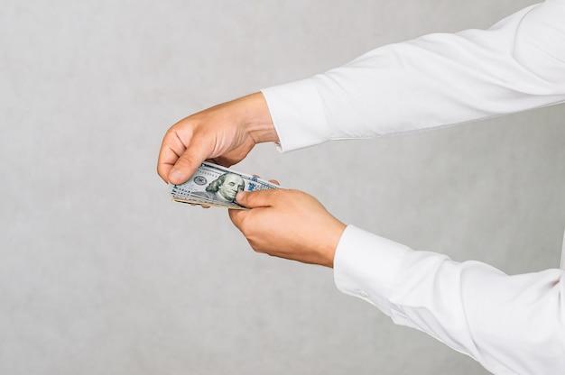 Деньги в руках мужчины. на светлом фоне.