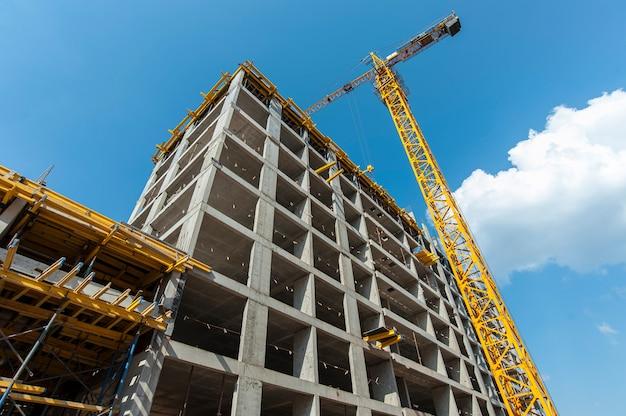 Монолитный каркас строящегося нового дома на фоне крана и голубого неба.