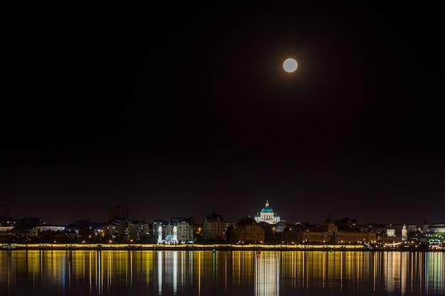 하늘의 달과 물에 비친 도시의 모습