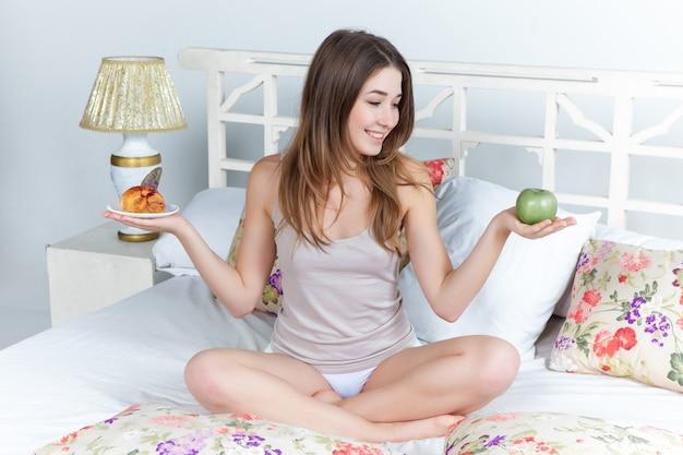 自宅のベッドで若い美しい少女の朝と朝食