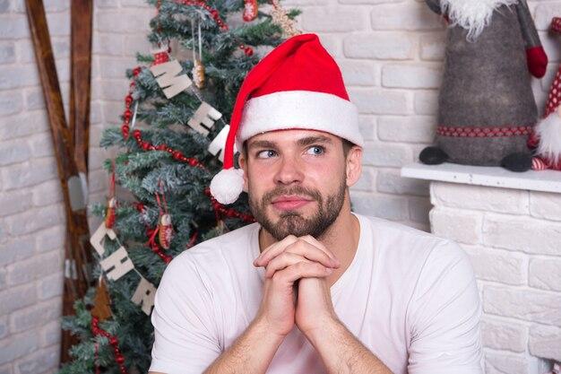 Утро перед рождеством. счастливый человек санта. рождественские покупки онлайн. новогодняя сцена с деревом и подарками. человек в новогодней шапке ждет рождественского подарка. доставка рождественских подарков. офисная рождественская вечеринка.