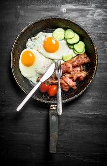 朝はフォーク付きのフライパンで朝食。ベーコン、豆、きゅうりの目玉焼き。黒い木製の背景に。