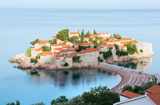 Утренний вид на морской островок свети-стефан с пляжем и городком-отелем (черногория, 6 км к юго-востоку от будвы)