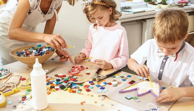 子供のためのモザイクパズルアート、子供たちの創造的なゲーム。手はテーブルでモザイクを遊んでいます。カラフルなマルチカラーのディテールをクローズアップ。創造性、子供の発達と学習のコンセプト
