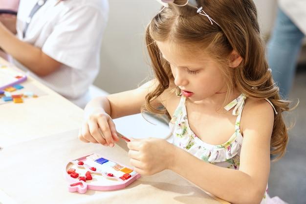 Мозаика-пазл для детей, детская творческая игра. руки играют в мозаику за столом. красочные разноцветные детали крупным планом. концепция творчества, развития и обучения детей