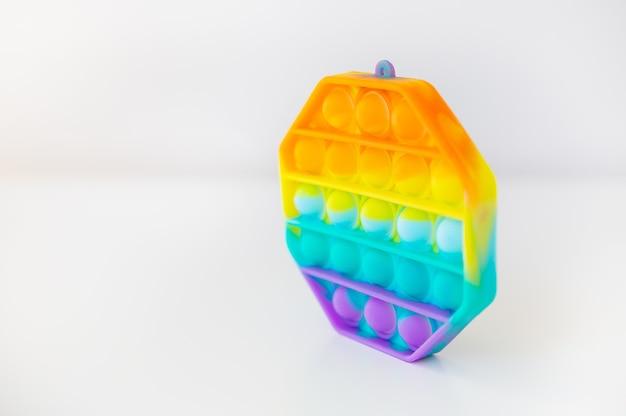 最もファッショナブルな感覚玩具。新しい人気のカラフルな六角形のポップイットアンチストレスおもちゃ。そわそわおもちゃレインボーポップ、テキストの場所。側面図。