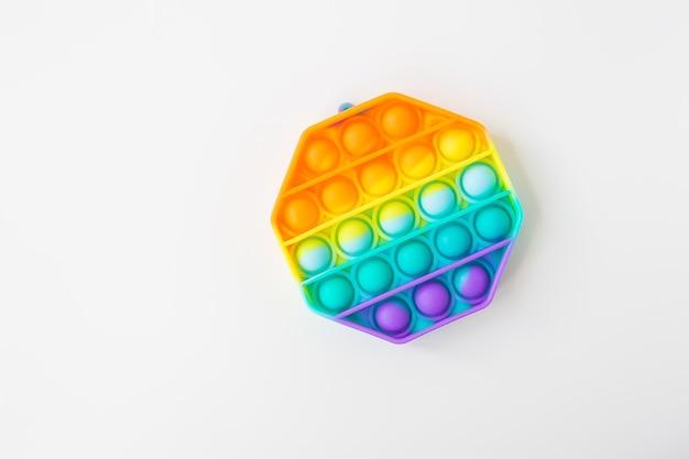 最もファッショナブルな感覚玩具。人気のカラフルな六角形のポップイットアンチストレス玩具。おもちゃのそわそわレインボーポップ、テキストの場所。