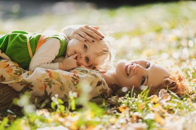 母と娘は草の上に横たわっています
