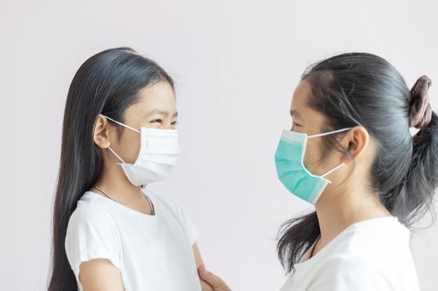 母と娘は防護マスクを着用しています。