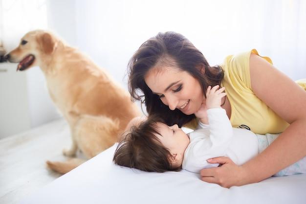 Мать обнимает свою дочь и лежит на кровати