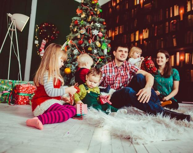 母、父、子供たちがクリスマスツリーの近くに座っている