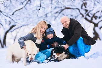 The mother, father, son and dogs sitting on the snow