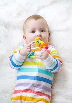 엄마는 아기에게 딸랑이를 준다. 선택적 초점. 아이.