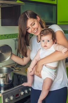 아기를 둔 여성의 어머니가 스토브의 냄비에 음식을 요리합니다.