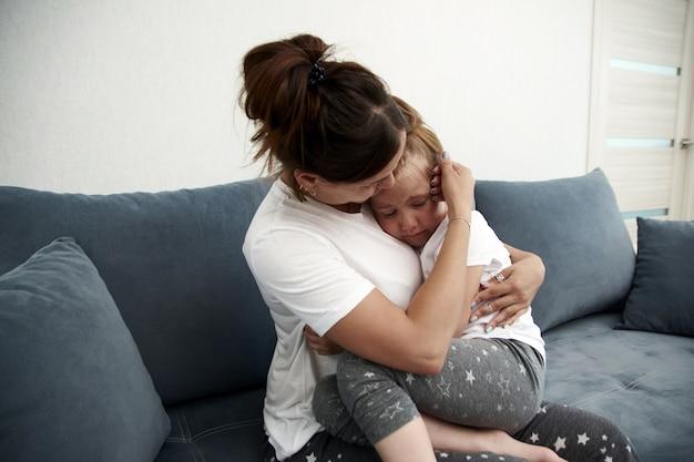 Мать жалеет дочь. маленькая девочка грустит. мать успокаивает маленькую девочку