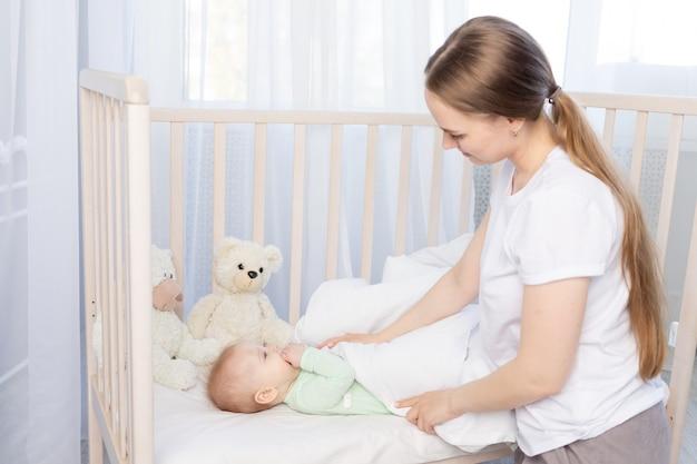 母親は赤ちゃんを毛布で覆っているベビーベッドで眠らせます。