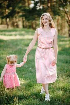 Мать бегает с дочерью и держит ее за руку на природе в летний день, каникулы. мама и девочка гуляют и играют в парке во время заката. понятие дружной семьи. закройте вверх.