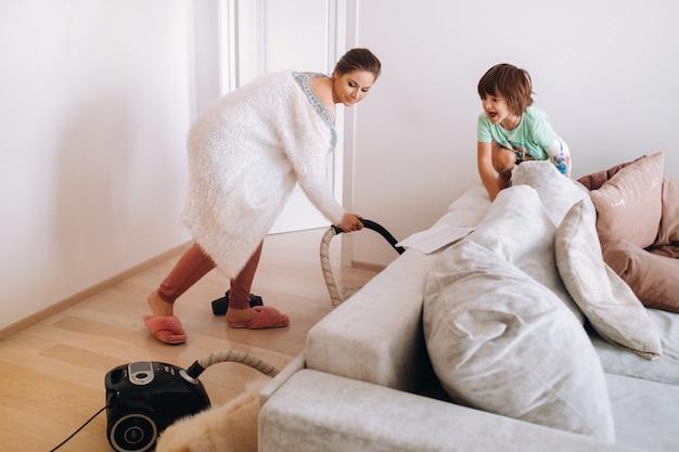 Мать пылесосит пол дома, а сын смотрит на это и смеется.