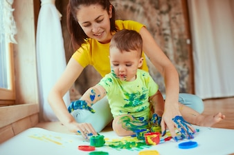The mother with son painting a big paper with their hands