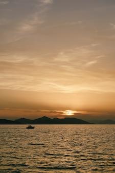 モーターボートは山の近くの夕日を背景に水に浮かんでいます