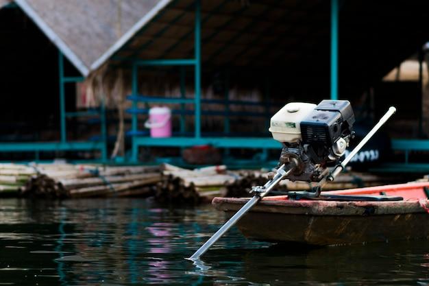 モーターボートは水面に浮かんでおり、背景には浮き筏があります。