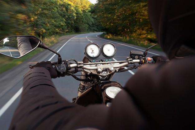 モーターサイクリストは夕方に空のアスファルト道路を走っています