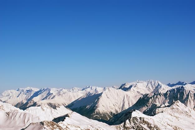 눈 속의 산, 구름이있는 하늘, 눈 덮인 가문비 나무 프리미엄 사진