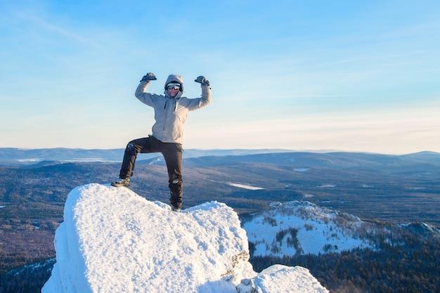 등산가는 산 정상에 올랐고, 남자 등산객은 바위 정상에 서서 성공을 축하합니다