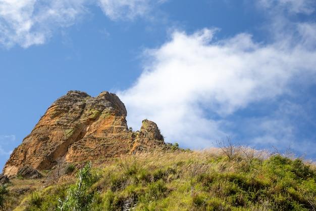 Горы, покрытые растениями, и голубое небо с небольшими облаками